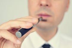 Junger Mann, der mit einer elektronischen Zigarette vaping ist Stockbilder