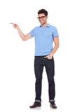 Junger Mann, der mit einer Hand in der Tasche zeigt Stockfotografie