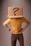 Junger Mann, der mit einer Pappschachtel auf seinem Kopf gestikuliert Stockfotos