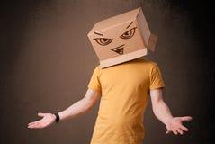 Junger Mann, der mit einer Pappschachtel auf seinem Kopf mit Übel f gestikuliert Stockfotografie