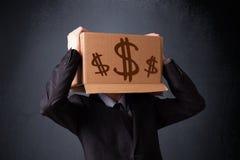 Junger Mann, der mit einer Pappschachtel auf seinem Kopf mit Dollar gestikuliert Stockfotos