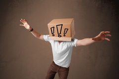 Junger Mann, der mit einer Pappschachtel auf seinem Kopf mit exclam gestikuliert Lizenzfreies Stockbild