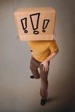 Junger Mann, der mit einer Pappschachtel auf seinem Kopf mit exclam gestikuliert Stockfoto