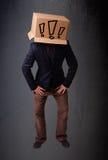 Junger Mann, der mit einer Pappschachtel auf seinem Kopf mit exclam gestikuliert Lizenzfreies Stockfoto