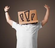 Junger Mann, der mit einer Pappschachtel auf seinem Kopf mit exclam gestikuliert Lizenzfreie Stockfotos