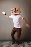Junger Mann, der mit einer Pappschachtel auf seinem Kopf mit exclam gestikuliert Stockfotos