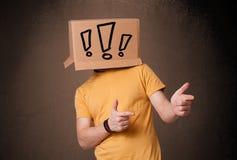 Junger Mann, der mit einer Pappschachtel auf seinem Kopf mit exclam gestikuliert Lizenzfreie Stockfotografie