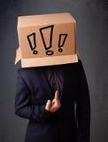 Junger Mann, der mit einer Pappschachtel auf seinem Kopf mit exclam gestikuliert Stockfotografie