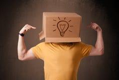 Junger Mann, der mit einer Pappschachtel auf seinem Kopf mit Licht gestikuliert Lizenzfreie Stockfotografie