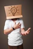 Junger Mann, der mit einer Pappschachtel auf seinem Kopf mit Licht gestikuliert Lizenzfreies Stockbild