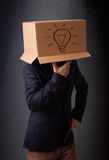 Junger Mann, der mit einer Pappschachtel auf seinem Kopf mit Licht gestikuliert Stockfoto