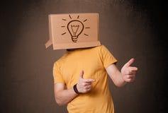 Junger Mann, der mit einer Pappschachtel auf seinem Kopf mit Licht gestikuliert Lizenzfreie Stockbilder