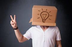 Junger Mann, der mit einer Pappschachtel auf seinem Kopf mit Licht gestikuliert Stockfotografie
