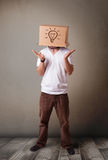 Junger Mann, der mit einer Pappschachtel auf seinem Kopf mit Licht gestikuliert Lizenzfreies Stockfoto