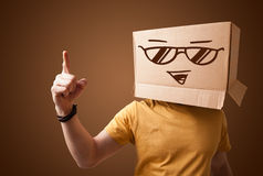 Junger Mann, der mit einer Pappschachtel auf seinem Kopf mit smiley gestikuliert Lizenzfreies Stockfoto