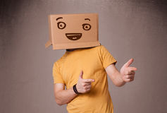 Junger Mann, der mit einer Pappschachtel auf seinem Kopf mit smiley gestikuliert Lizenzfreies Stockbild