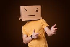 Junger Mann, der mit einer Pappschachtel auf seinem Kopf mit straig gestikuliert Lizenzfreie Stockfotografie