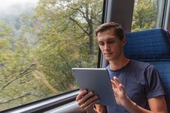 Junger Mann, der mit einer Tablette beim Reisen mit dem Zug studiert stockfotografie