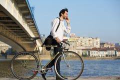 Junger Mann, der mit Fahrrad geht und auf Mobiltelefon spricht Stockbilder