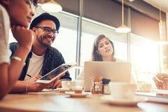 Junger Mann, der mit Freunden an einem Café sitzt und spricht Lizenzfreie Stockfotografie