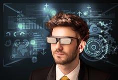 Junger Mann, der mit futuristischen intelligenten High-Techen Gläsern schaut Stockbild