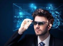 Junger Mann, der mit futuristischen intelligenten High-Techen Gläsern schaut Lizenzfreies Stockfoto