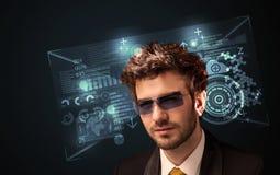 Junger Mann, der mit futuristischen intelligenten High-Techen Gläsern schaut Lizenzfreie Stockbilder