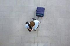 Junger Mann, der mit Gepäck am Flughafen geht Stockbild