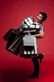 Junger Mann, der mit Geschenken lächelt Lizenzfreies Stockfoto