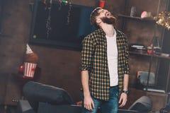 Junger Mann, der mit geschlossenen Augen steht und im unordentlichen Raum nach Partei schreit Stockfotos