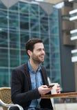 Junger Mann, der mit Handy lächelt Lizenzfreie Stockfotos
