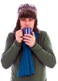 Junger Mann, der mit heißem Tee aufwärmt Stockfoto