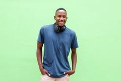 Junger Mann, der mit Kopfhörern gegen grünen Hintergrund lächelt lizenzfreies stockfoto