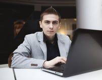 Junger Mann, der mit Laptop arbeitet stockbild
