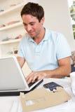 Junger Mann, der mit Laptop-Computer arbeitet Lizenzfreie Stockbilder