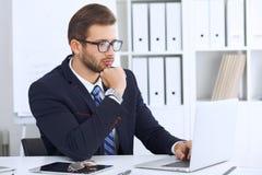 Junger Mann, der mit Laptop-Computer, Mann ` s Hände auf Notizbuch, Geschäftsperson am Arbeitsplatz arbeitet Stockbild