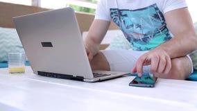 Junger Mann, der mit Laptop im Café arbeitet stock footage