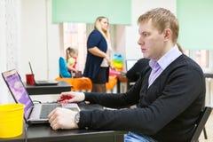 Junger Mann, der mit Laptop im Funktionsraum arbeitet Stockfotos