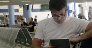 Junger Mann, der mit Notenauflage am Flughafen arbeitet stock video