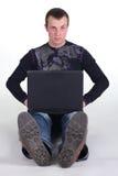 Junger Mann, der mit Notizbuch sitzt Stockfoto