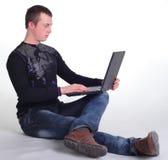 Junger Mann, der mit Notizbuch sitzt Stockbild
