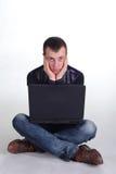 Junger Mann, der mit Notizbuch sitzt Lizenzfreies Stockfoto