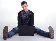Junger Mann, der mit Notizbuch sitzt Stockfotografie
