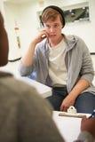 Junger Mann, der mit Ratsmitglied spricht, das Kenntnisse nimmt Stockbild