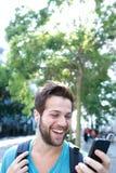 Junger Mann, der mit Rucksack lächelt und Handy betrachtet Lizenzfreie Stockbilder