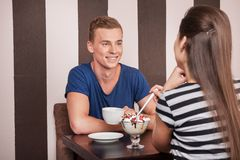 Junger Mann, der mit schönem Mädchen sitzt stockfotos