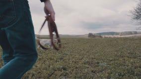 Junger Mann, der mit seinem gelben Labrador über dem Feld geht stock video