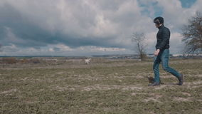 Junger Mann, der mit seinem gelben Labrador über dem Feld geht stock video footage