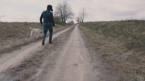 Junger Mann, der mit seinem Hund entlang dem Schotterweg geht stock video footage