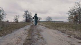 Junger Mann, der mit seinem Hund entlang dem Schotterweg geht stock footage